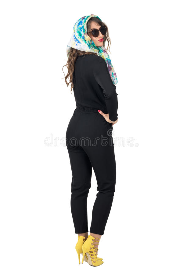 Fashion model wearing sunglasses and headscarf with hands on hips back view turn around. Full body length portrait isolated over white studio background stock image