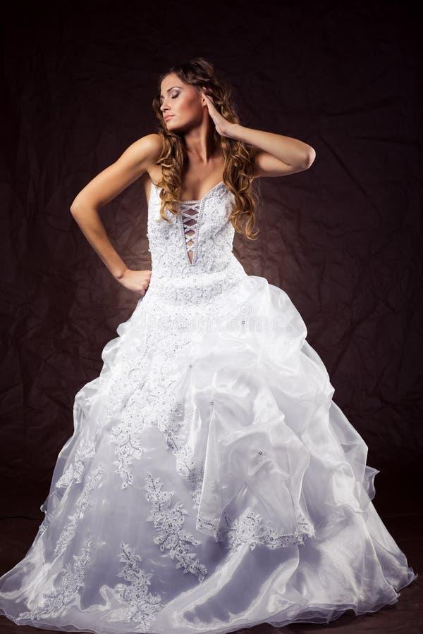 Fashion model wearing wedding dress. At brown studio background royalty free stock photos