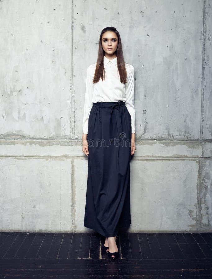 Fashion model wearing white shirt and long black skirt posing in studio. On concrete wall stock photo