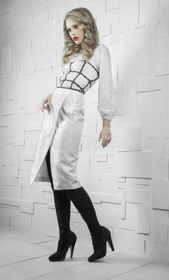 Fashion model in white suit. In light room royalty free stock photography