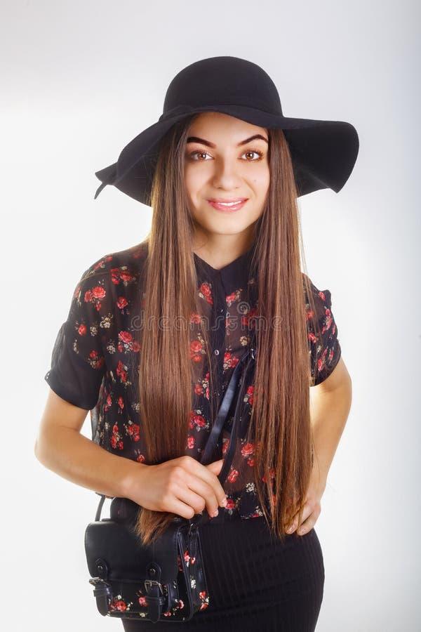 Fashion model woman in black hat, black mini skirt posing on white background.  royalty free stock photography