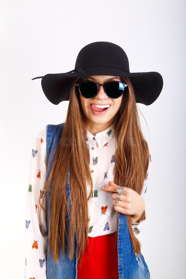 Fashion model woman in black hat, sunglasses, red mini skirt posing on white background.  stock photo