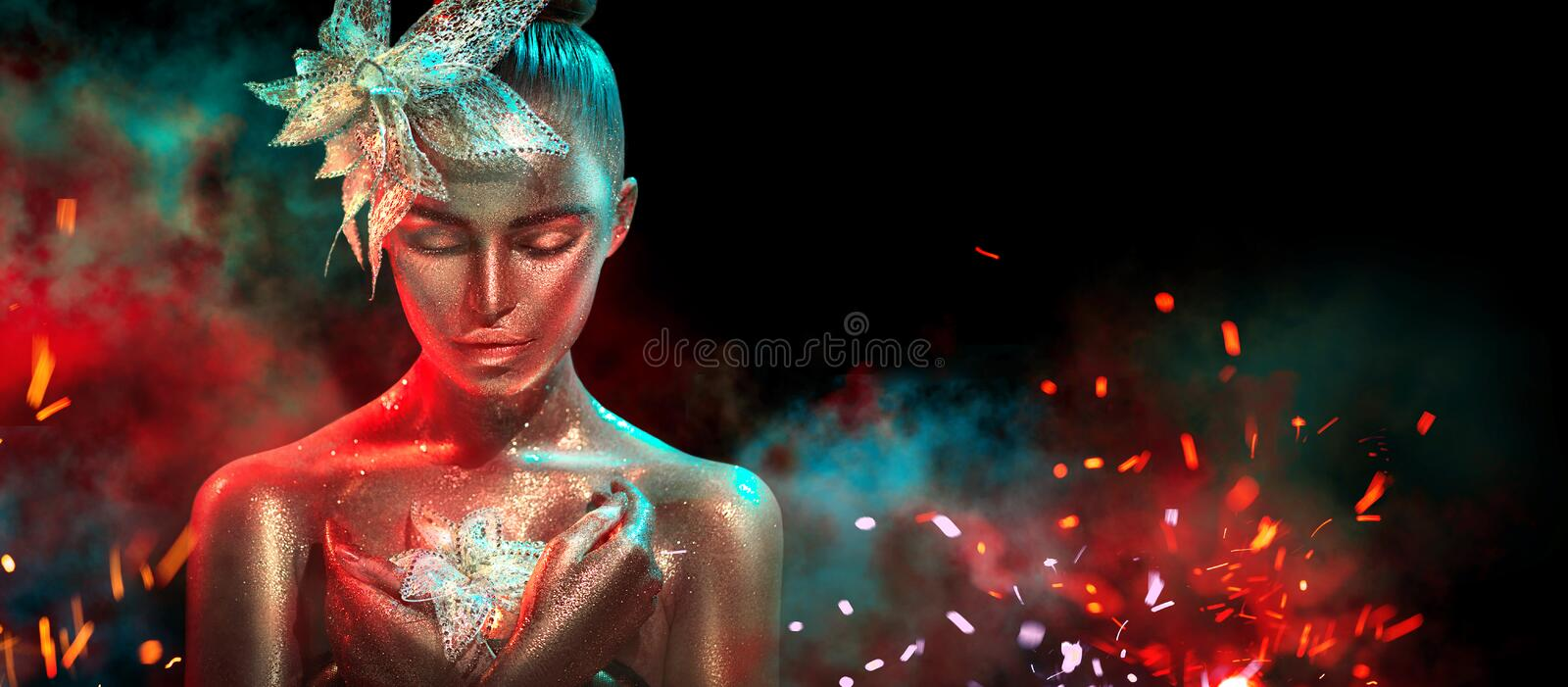 Fashion model woman in colorful bright golden sparkles and neon lights posing with fantasy flower. Portrait of beautiful girl stock images