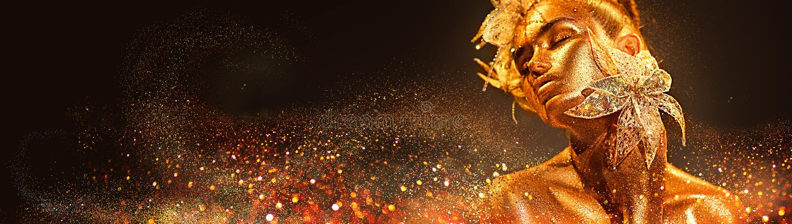 Fashion model woman in colorful bright golden sparkles posing with fantasy flower. Portrait of beautiful girl with glowing makeup stock photography
