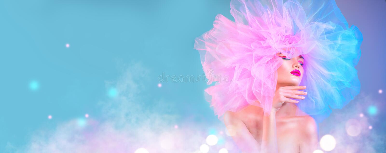 Fashion model woman in colorful bright lights posing, portrait of beautiful girl with trendy makeup and colorful pink hairdo. Art design stock photography