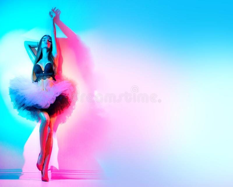 Fashion model woman in colorful bright neon lights dancing in night club in tulle skirt, high heels. Full length Portrait stock images