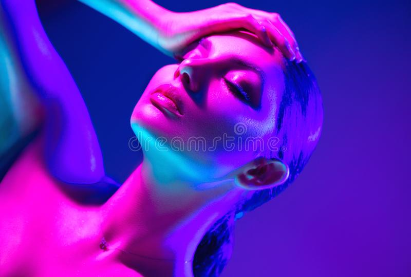 Fashion model woman in colorful bright neon lights posing in studio. Portrait of beautiful sexy dancing girl in UV. Art design colorful makeup royalty free stock photos