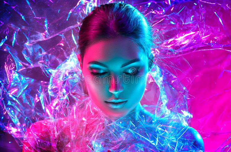 Fashion model woman in colorful bright neon lights posing in studio through transparent film. Portrait of beautiful sexy girl stock image