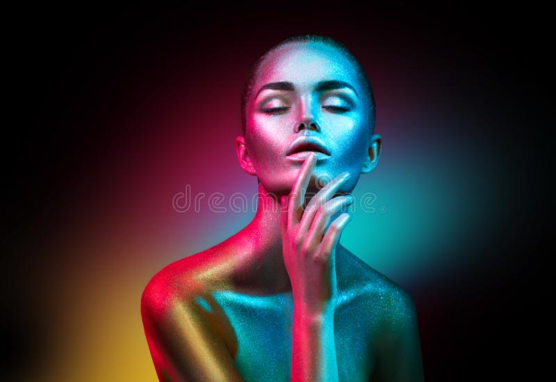 Fashion model woman in colorful bright sparkles and neon lights posing in studio, portrait of beautiful girl stock images