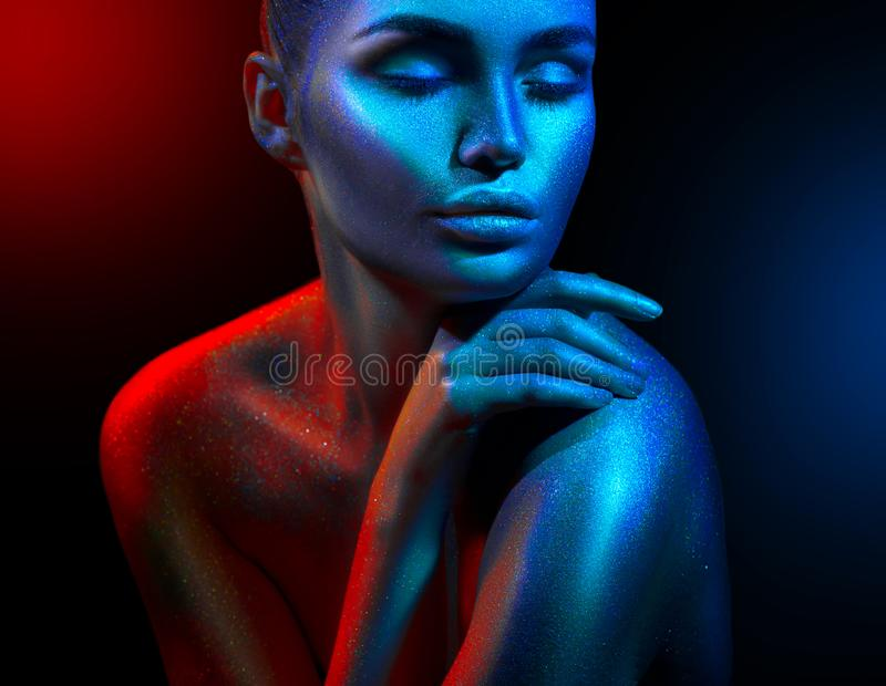Fashion model woman in colorful bright sparkles and neon lights posing in studio, portrait of beautiful girl. Art design colorful vivid makeup royalty free stock image