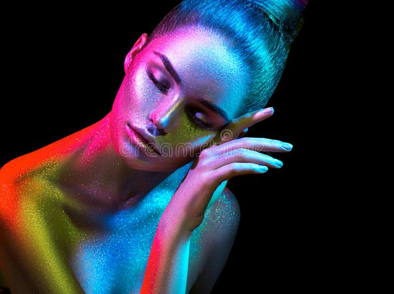 Fashion model woman in colorful bright sparkles and neon lights posing in studio, portrait of beautiful girl. Art design colorful vivid makeup royalty free stock photos