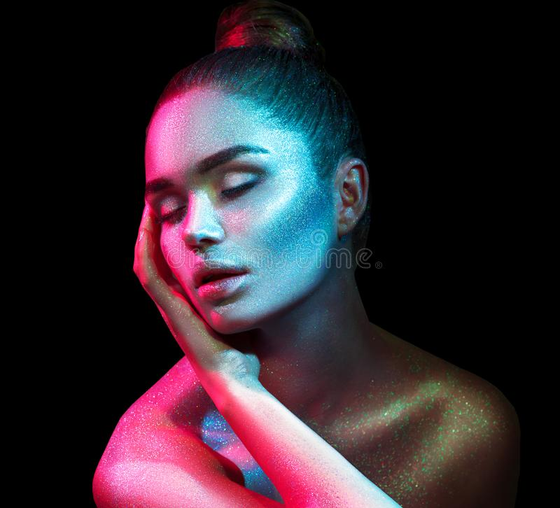 Fashion model woman in colorful bright sparkles and neon lights posing in studio, portrait of beautiful girl. Art design colorful vivid makeup royalty free stock photography
