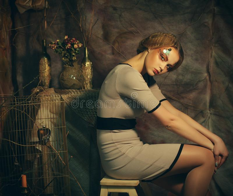 Fashion model woman with creative make up sitting on a stool in drama decoration royalty free stock images