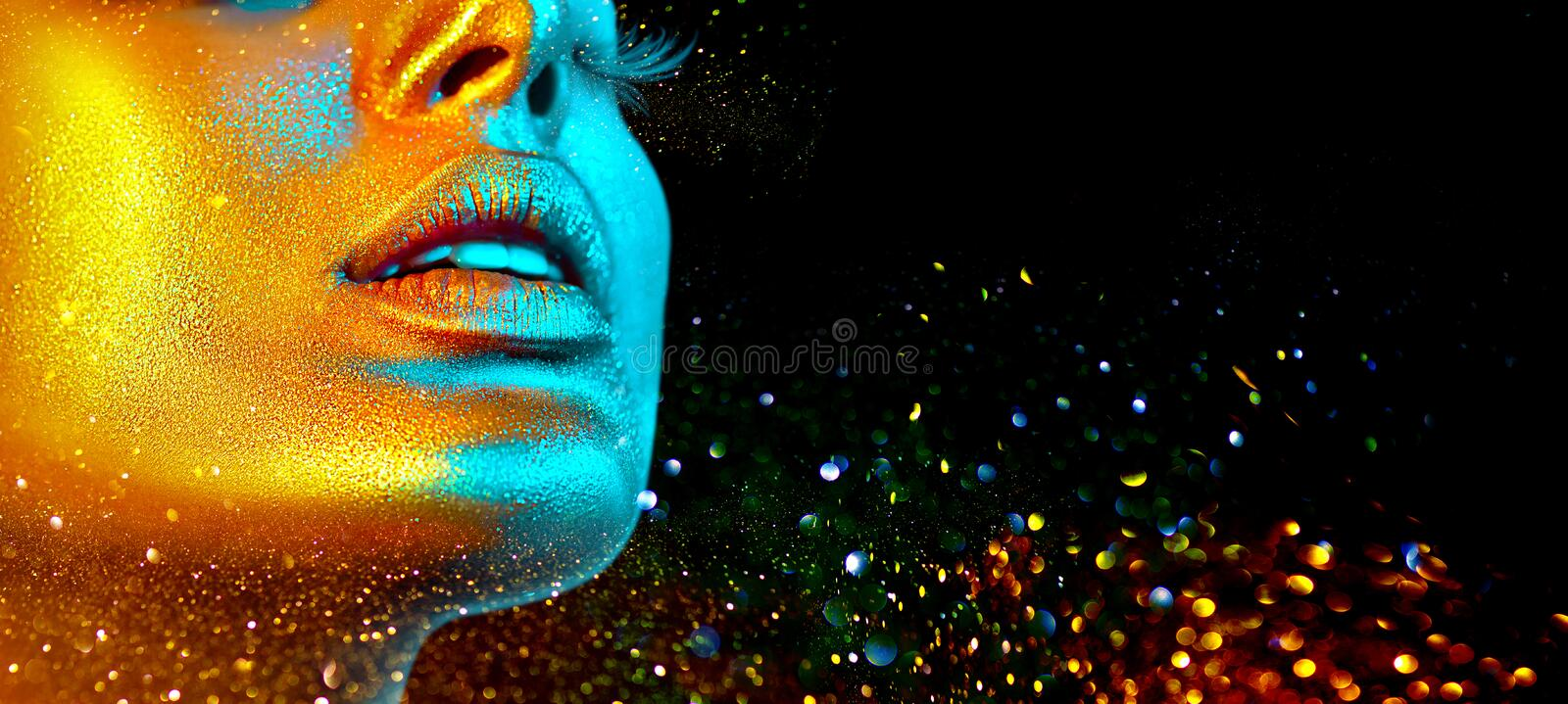 Fashion model woman face in bright sparkles, colorful neon lights, beautiful sexy girl lips. Trendy glowing gold skin royalty free stock photo
