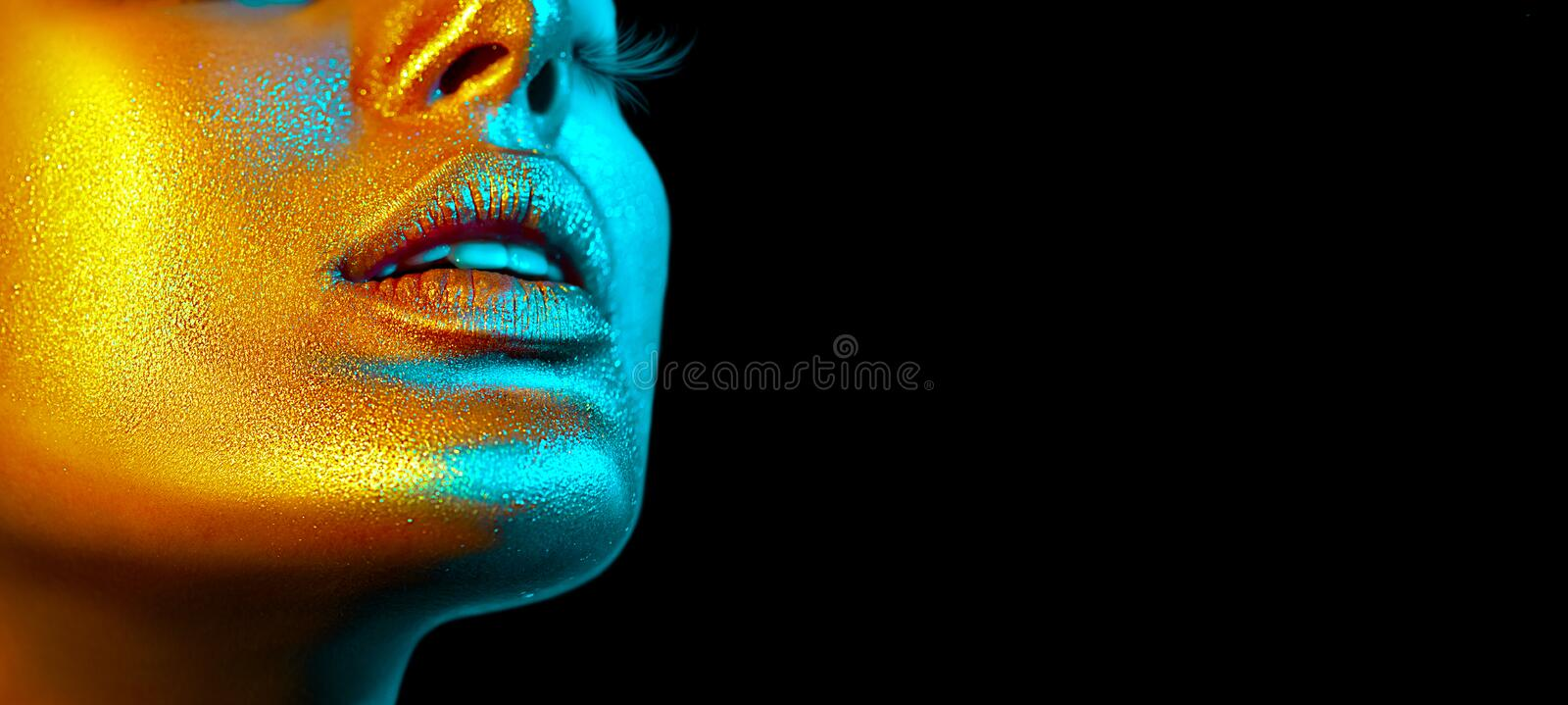 Fashion model woman face in bright sparkles, colorful neon lights, beautiful sexy girl lips. Trendy glowing gold skin make-up. Glitter metallic shine makeup royalty free stock photos