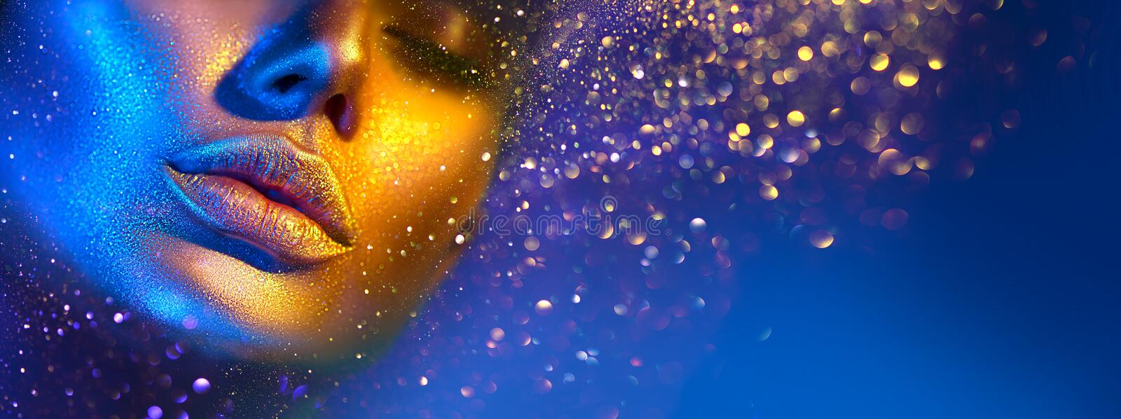 Fashion model woman face in bright sparkles, colorful neon lights, beautiful sexy girl lips. Trendy glowing gold skin makeup. Fashion model woman face in bright stock images