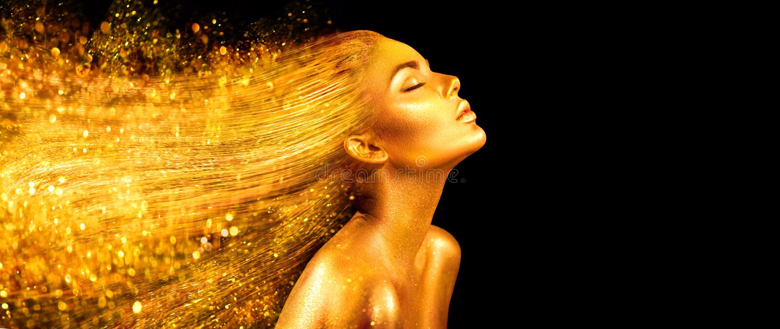 Fashion model woman in golden bright sparkles. Girl with golden skin and hair portrait closeup royalty free stock images