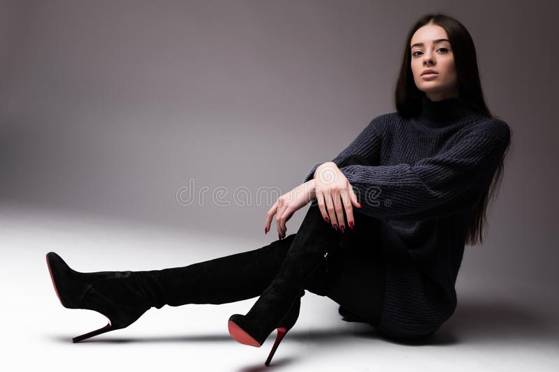 Fashion model woman in modern clothes sitting on the floor isolated on white background stock images