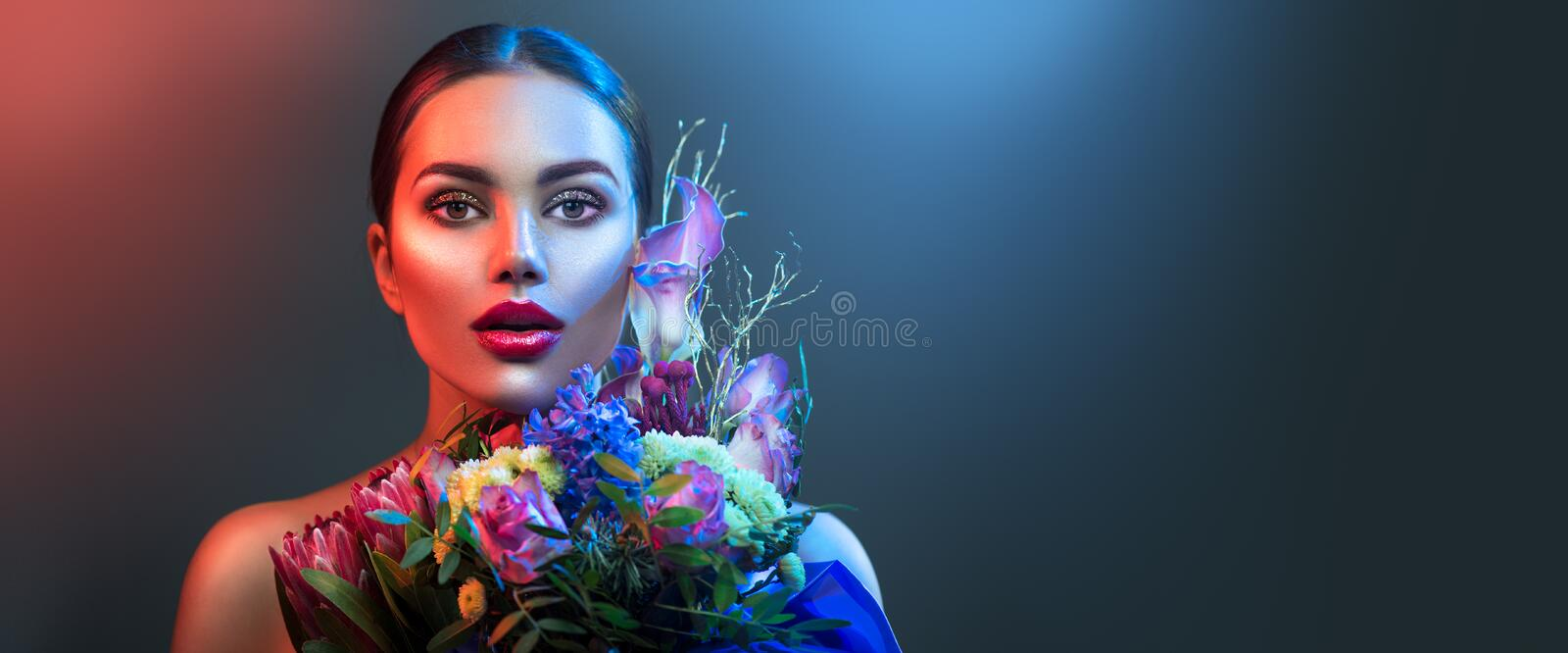 Fashion model woman in neon light. Beautiful model girl with colorful bright fluorescent makeup. On dark background. Valentine`s day stock photo