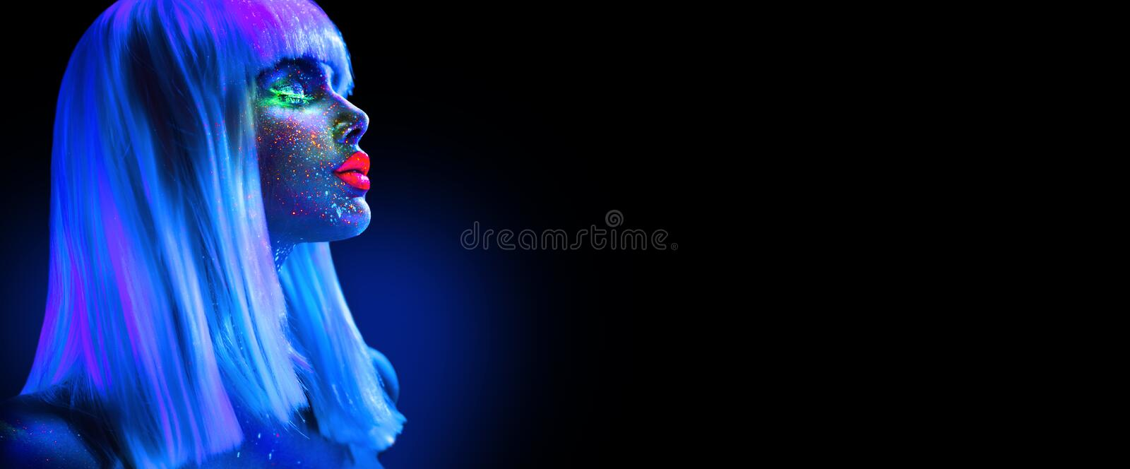 Fashion model woman in neon light. Beautiful model girl with colorful bright fluorescent makeup isolated on black. Ultraviolet. UV royalty free stock images
