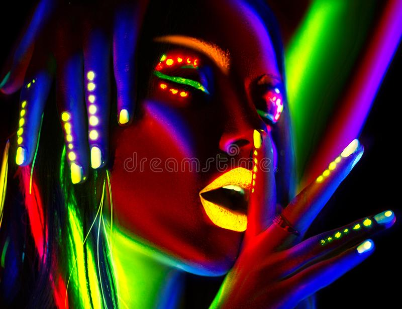 Fashion model woman in neon light. Beautiful model girl with colorful fluorescent makeup. Fashion model woman in neon light. Portrait of beautiful model girl stock photos