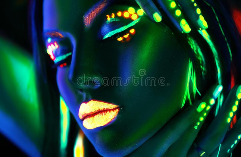 Fashion model woman in neon light. Beautiful model girl with colorful fluorescent makeup. Fashion model woman in neon light. Portrait of beautiful model girl stock images