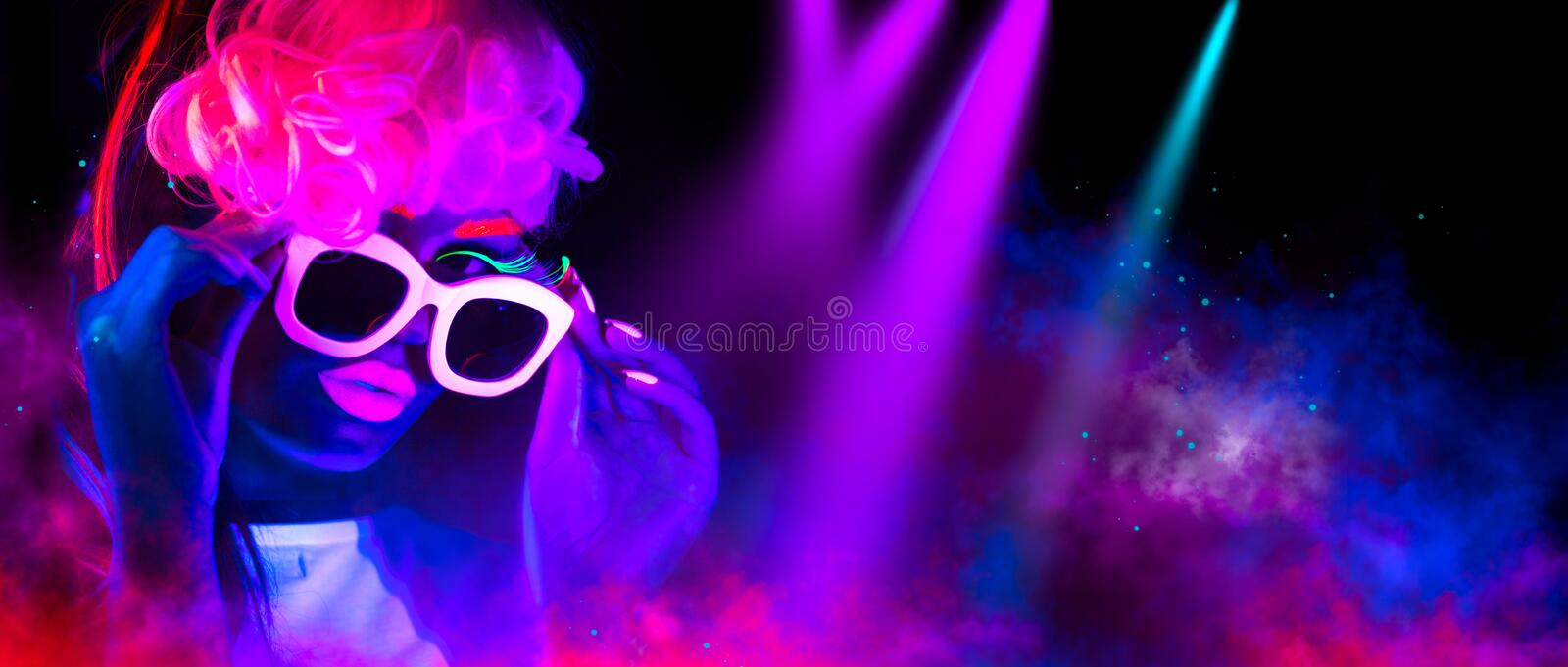 Fashion model woman in neon light. Portrait of beautiful model girl with colorful fluorescent makeup. Fashion model woman in neon light. Disco dancer. Portrait stock image