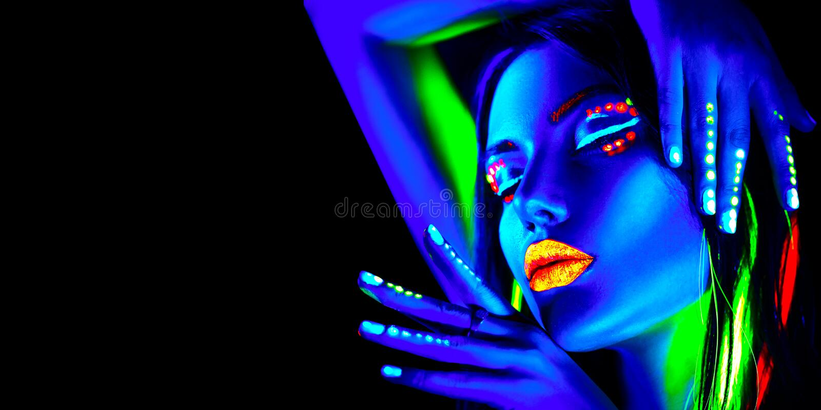 Fashion model woman in neon light, portrait of beautiful model girl with fluorescent makeup, Body art design in UV. Painted face, colorful make up, over black royalty free stock photography