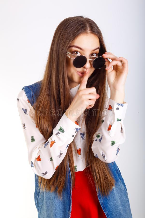 Fashion model woman in sunglasses, red mini skirt posing on white background, holding finger near lips.  royalty free stock images