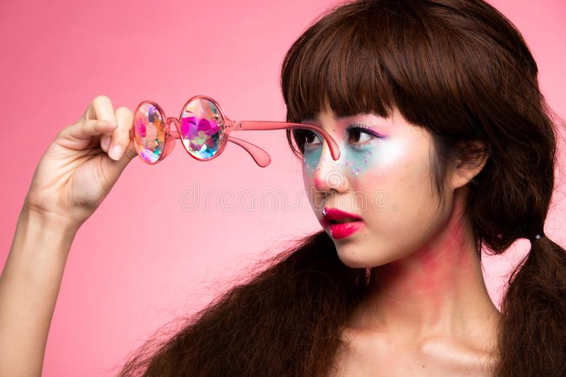 Fashion Model Woman wear Kaleidoscope Glasses. Fashion Model looks at camera for shooting new collection Sunglasses.  Beautiful Asian Woman summer trend make up stock photo