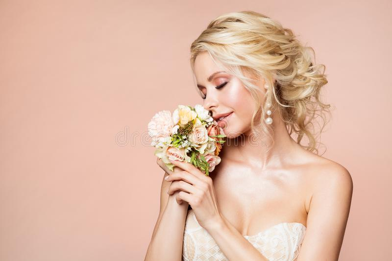 Fashion Models Beauty Portrait, Woman Smelling Flowers Bouquet, Beautiful Makeup and Hairstyle, Girl Studio Shot on Beige stock photography