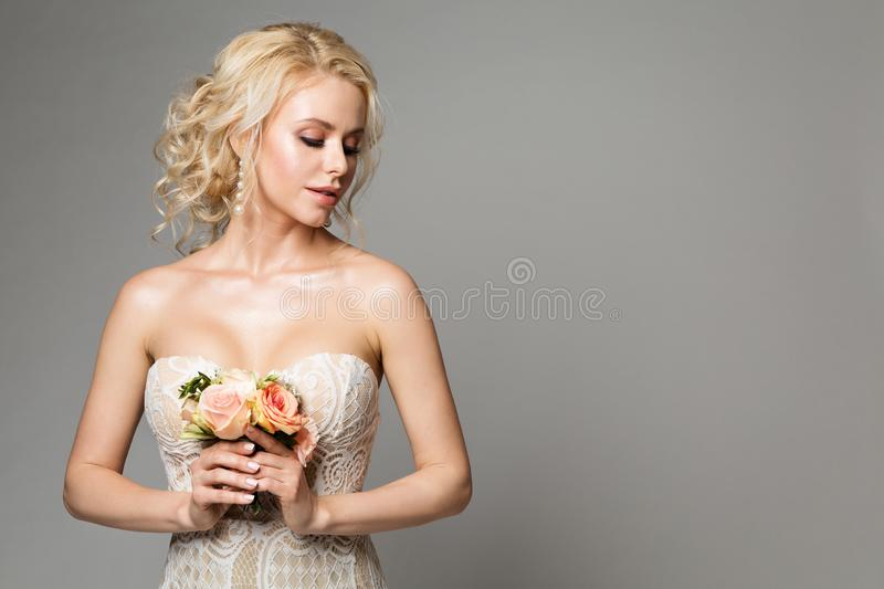 Fashion Models Portrait with Flower Bouquet, Beautiful Woman Bride Makeup and Hairstyle, Girl studio shot on gray stock photo