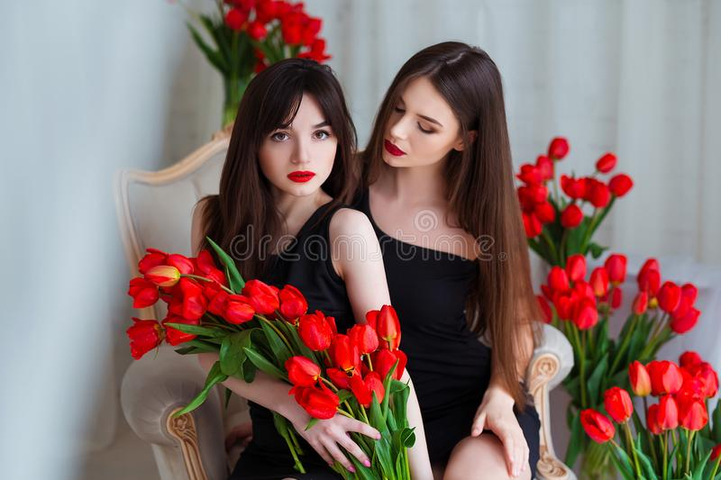 Fashion models in tender black dresses posing in sensual way at luxury interior full of tulips. Young woman sensuality. royalty free stock photography