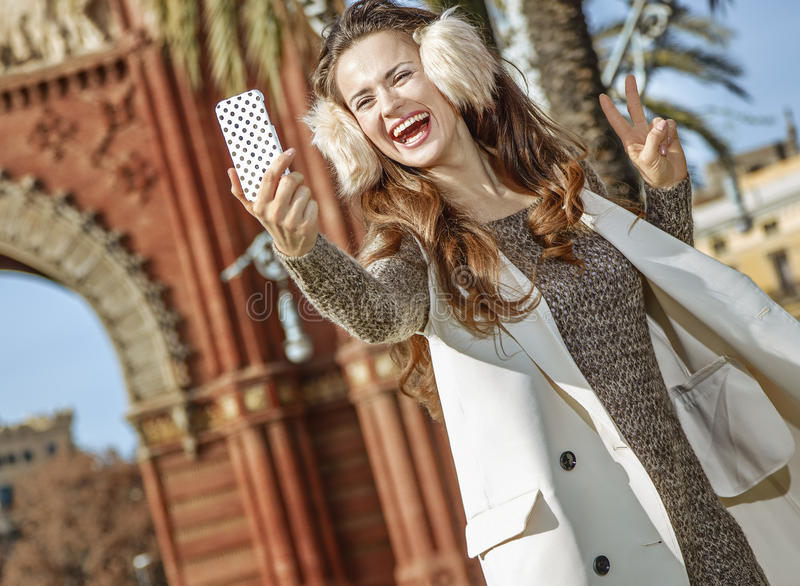 Fashion-monger taking selfie and showing victory gesture. In Barcelona for a perfect winter. smiling elegant fashion-monger in earmuffs in Barcelona, Spain with royalty free stock images