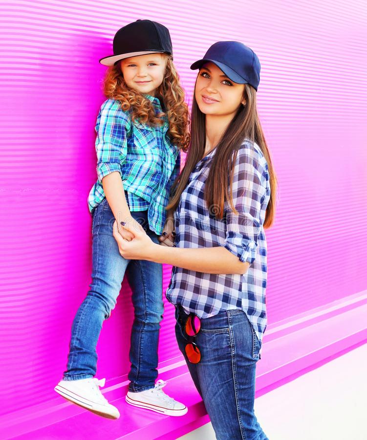 Fashion mother and child little girl in checkered shirts and baseball caps in city on colorful pink wall royalty free stock photos