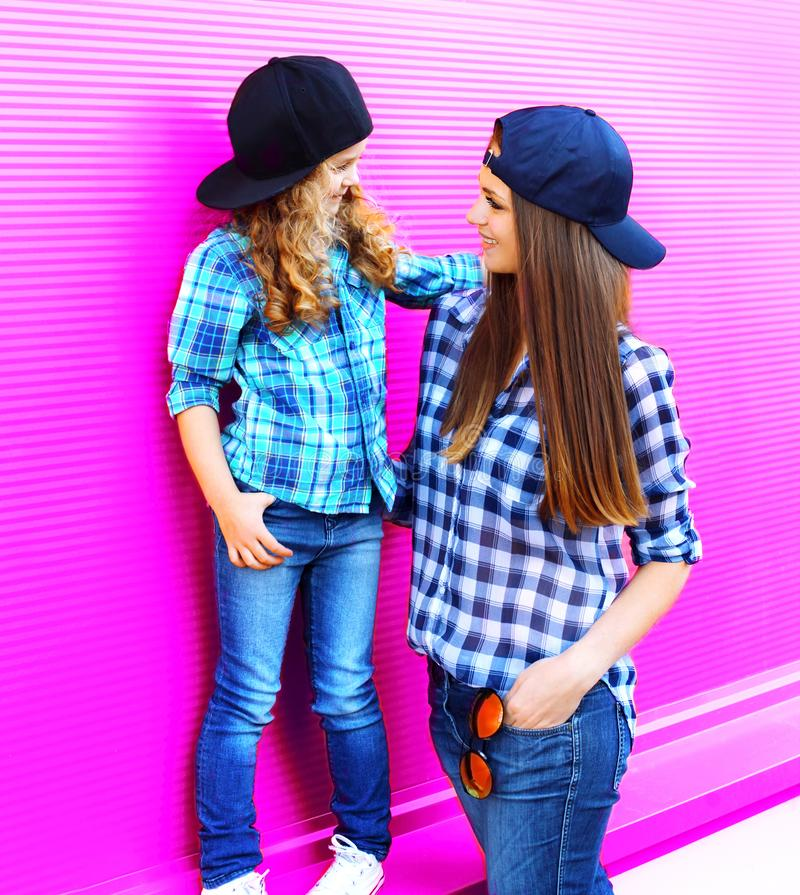 Fashion mother looking at child little girl in checkered shirts and baseball caps in city on colorful pink wall royalty free stock photography