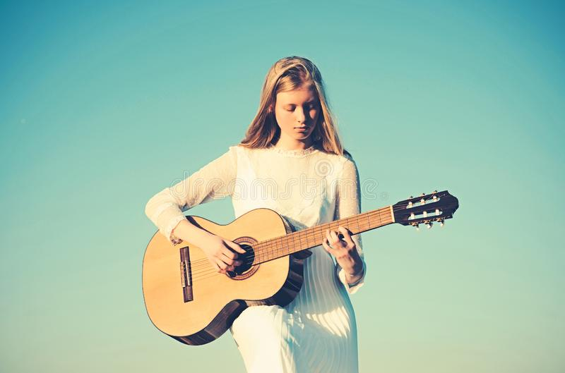 Fashion musician in white dress on sunny nature. Woman guitarist perform music concert. Albino girl hold acoustic guitar royalty free stock photos