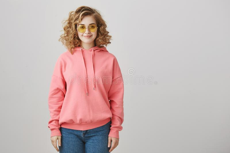 Fashion is in my blood. Good-looking caucasian girl with curly hair wearing trendy eyewear and pink hoodie, smiling and royalty free stock images