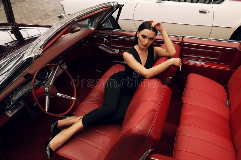 Beautiful girl with dark hair in elegant clothes posing in luxurious car. Fashion outdoor photo of beautiful girl with dark hair in elegant clothes posing in stock image