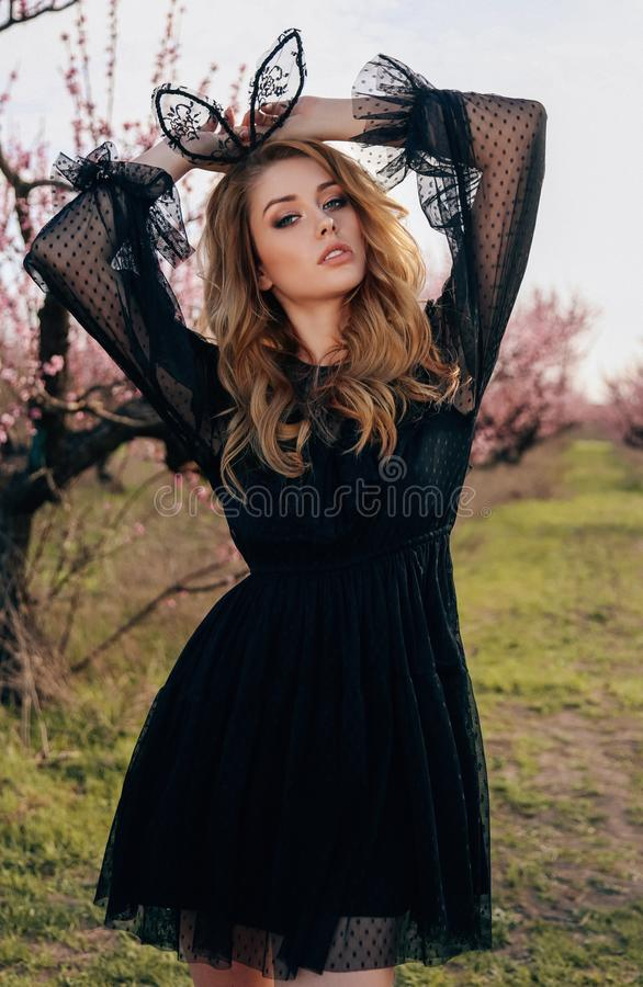 beautiful girl with blond hair in elegant dress posing in blooming peach garden stock image