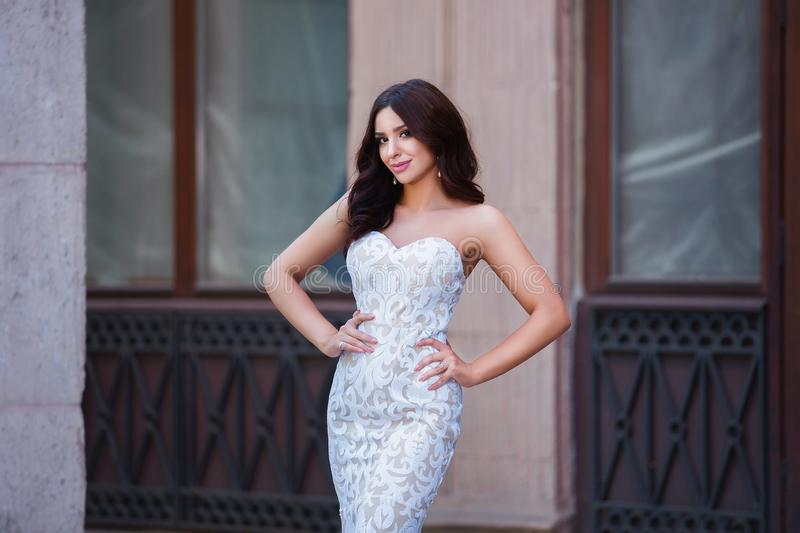 Fashion outdoor photo of beautiful sensual girl with dark hair in elegant dress posing in ancient architecture. royalty free stock photography
