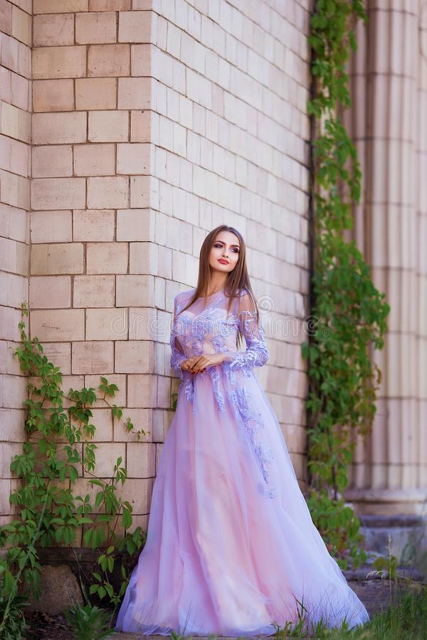 Fashion outdoor photo of beautiful sensual girl with dark hair in elegant dress posing in ancient architecture. royalty free stock image
