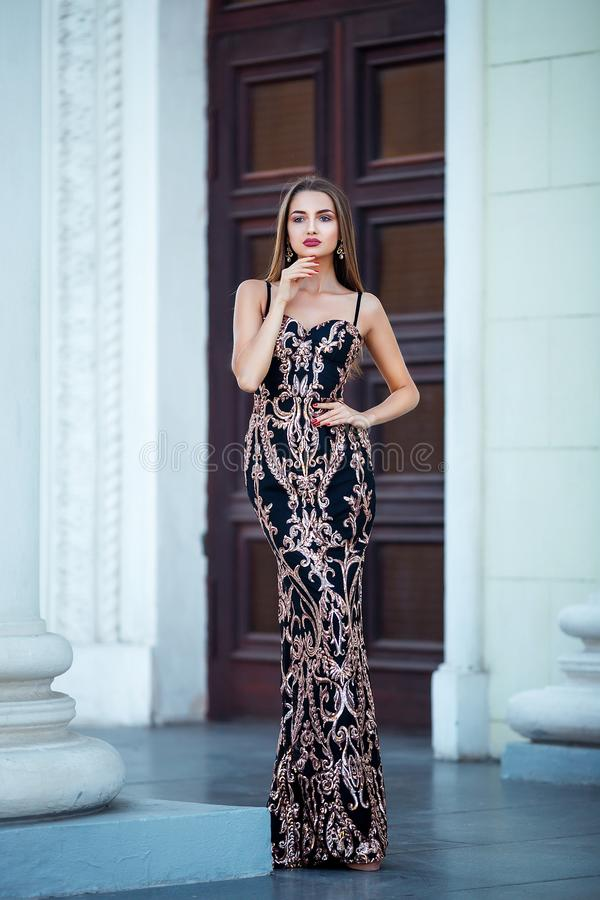 Fashion outdoor photo of beautiful sensual girl with dark hair in elegant dress posing in ancient architecture. stock photography