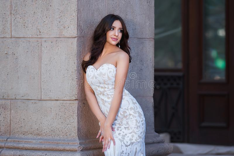 Fashion outdoor photo of beautiful sensual girl with dark hair in elegant dress posing in ancient architecture. stock photos