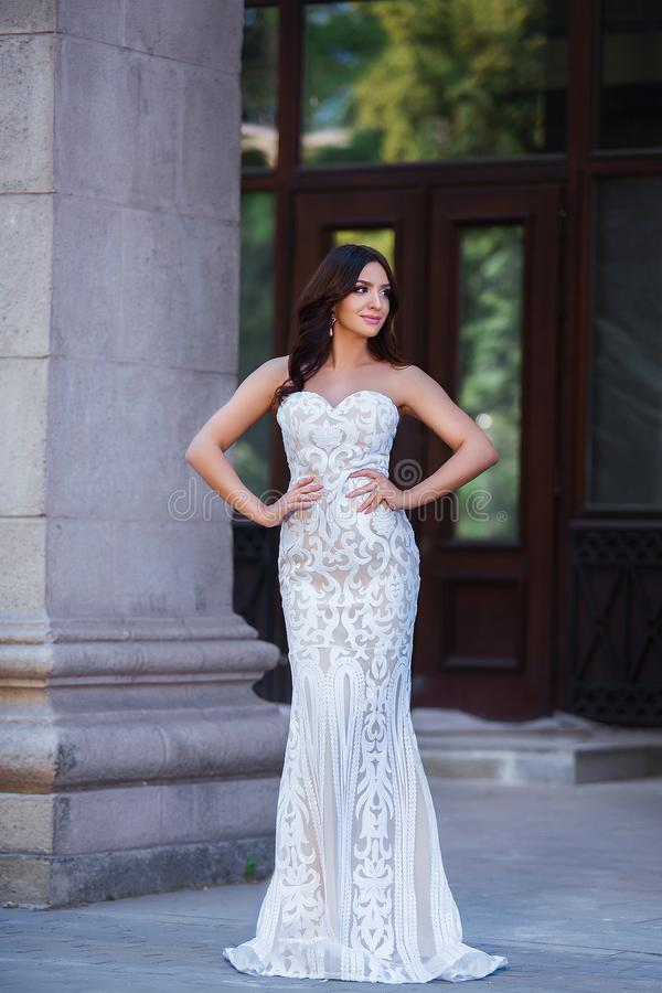 Fashion outdoor photo of beautiful sensual girl with dark hair in elegant dress posing in ancient architecture. royalty free stock photo