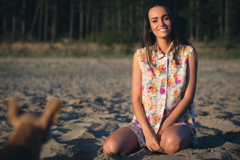 Fashion outdoor photo of beautiful sexy woman sitting on the sand with dark hair in light shirt stock image