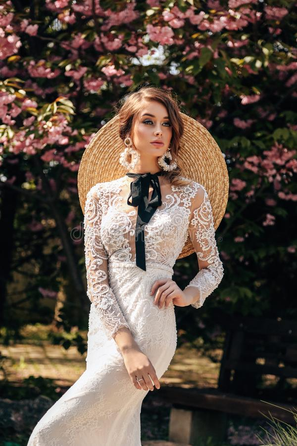 Beautiful woman with blond hair in luxurious wedding dresses with accessories posing in garden with blossoming sakura trees. Fashion outdoor photo of beautiful stock images
