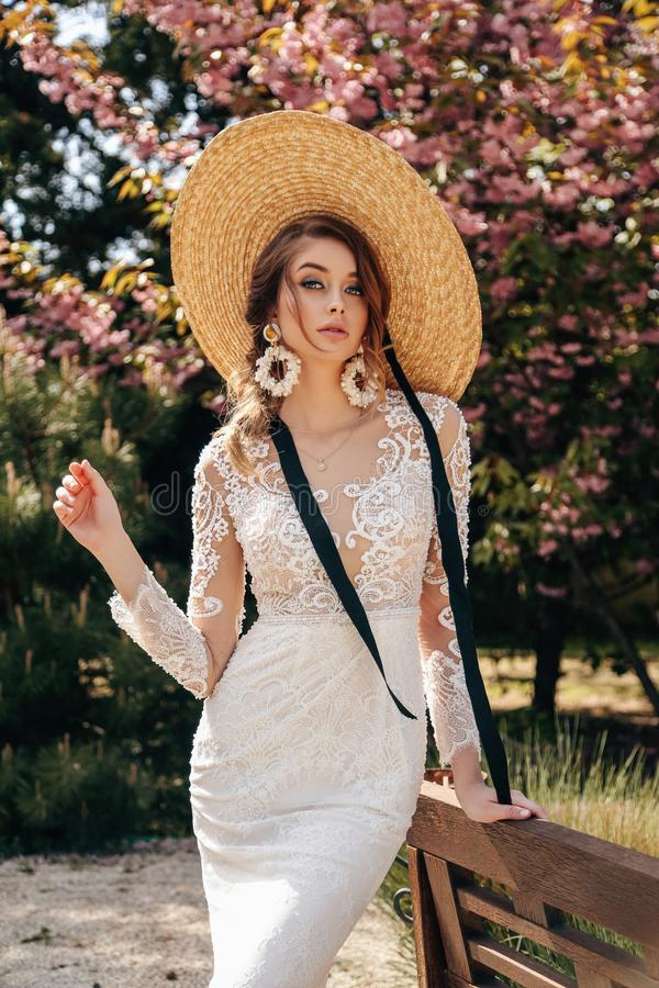 Beautiful woman with blond hair in luxurious wedding dresses with accessories posing in garden with blossoming sakura trees. Fashion outdoor photo of beautiful royalty free stock photo