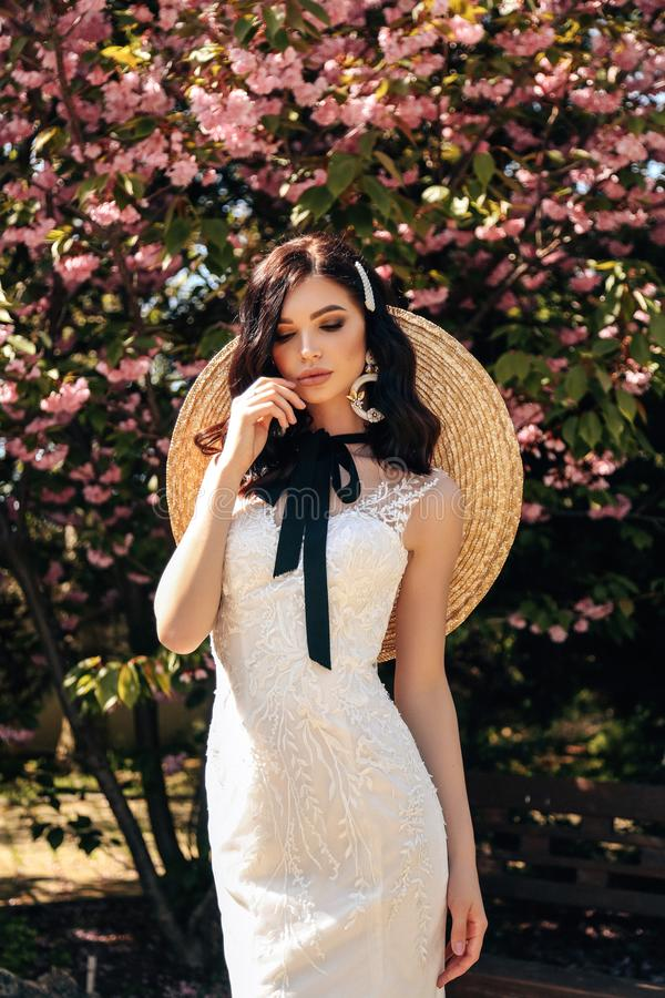 Beautiful woman with dark hair in luxurious wedding dresses with accessories posing in garden with blossoming sakura trees. Fashion outdoor photo of beautiful stock photos