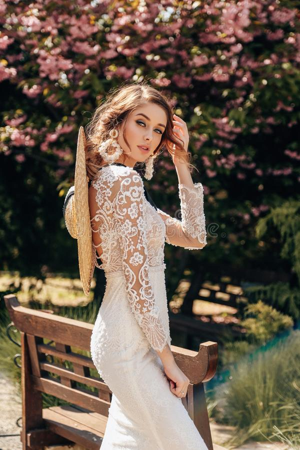 Beautiful woman with blond hair in luxurious wedding dresses with accessories posing in garden with blossoming sakura trees. Fashion outdoor photo of beautiful stock photography